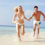 Couple Running Through Waves On Beach Holiday — Stock Photo #36836191