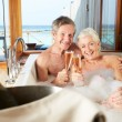 Senior Couple Relaxing In Bath Drinking Champagne Together — Stock Photo