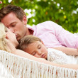 Stock Photo: Family Relaxing In Beach Hammock With Sleeping Daughter