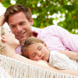 Family Relaxing In Beach Hammock With Sleeping Daughter — 图库照片