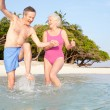 Senior Couple Splashing In Sea On Tropical Beach Holiday — Stock Photo