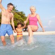 Grandparents With Granddaughter Splashing In Sea On Beach — Stock Photo #36836837