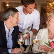 Stock Photo: Waiter Serving Wine To Senior Couple In Restaurant