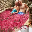 Senior Couple Relaxing In Flower Petal Covered Pool At Spa — Stock Photo