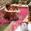 Couple Relaxing In Flower Petal Covered Pool At Spa — Stok fotoğraf