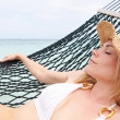 WomWearing Bikini And Sun Hat Relaxing In Beach Hammock — Stock Photo #36837361