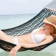 WomWearing Bikini And Sun Hat Relaxing In Beach Hammock — Stock Photo #36837371