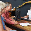 Hotel Receptionist Helping Senior Couple To Check In — Stock Photo