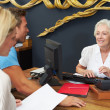 Hotel Receptionist Helping Couple To Check In — Stockfoto
