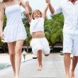 Parents Swinging Daughter As They Walk Along Wooden Jetty — Stock Photo