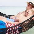 Grandfather And Grandson Relaxing In Beach Hammock — Stock Photo