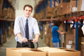 Businessman Pulling Pallet In Warehouse — Stock Photo