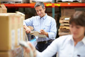 Manager In Warehouse With Worker Scanning Box In Foreground — Stock Photo