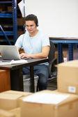 Arbetare i lager bära headsetet och med laptop — Stockfoto