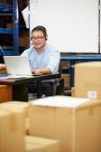 Trabalhador no armazém usando fone de ouvido e usando o laptop — Fotografia Stock