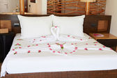 Hotel Bedroom With Flowers Arranged On Sheets — Stock Photo