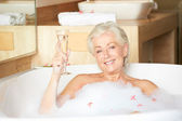 Senior Woman Relaxing In Bath Drinking Champagne — 图库照片