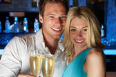 Couple Enjoying Glass Of Champagne In Bar — Stock Photo