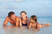 Family Lying In Sea On Tropical Beach Holiday — Stock Photo