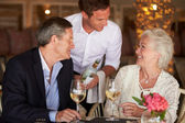 Waiter Serving Wine To Senior Couple In Restaurant — 图库照片