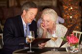 年长的夫妇从餐厅的菜单中选择 — 图库照片