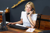 Hotel Receptionist Using Computer And Phone — Stock Photo