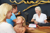 Hotel Receptionist Helping Family To Check In — Stock Photo