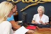 Hotel Receptionist Helping Couple To Check In — Stock Photo