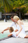 Family Sitting On Wooden Jetty — Stockfoto