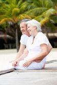 Senior Couple Sitting On Wooden Jetty — Stock Photo