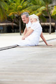 Senior Couple Sitting On Wooden Jetty — ストック写真