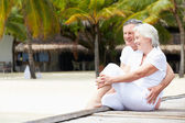 Senior Couple Sitting On Wooden Jetty — Stock fotografie