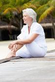 Senior Woman Sitting On Wooden Jetty — Stock Photo