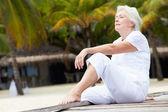 Senior Woman Sitting On Wooden Jetty — Stock fotografie