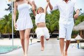 Parents Swinging Daughter As They Walk Along Wooden Jetty — Foto Stock