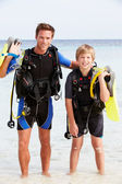 Father And Son With Scuba Diving Equipment On Beach Holiday — Stock Photo
