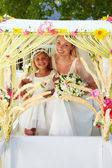 Bride And Bridesmaid Sitting Under Decorated Canopy — Stock Photo
