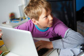 Boy Behaving Suspiciously Whilst Using Laptop — Stock Photo