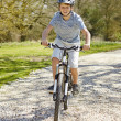 Stock Photo: Young Boy Riding Bike Along Country Track