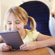Stock Photo: Little girl reading e-book
