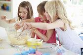Three Girls Making Cupcakes In Kitchen — Stock Photo