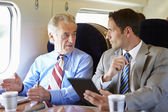 Businesspeople traveling by train — Stock Photo