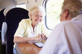 Senior couple traveling by train — Stock Photo