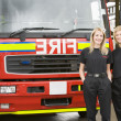 Portrait of two female firefighters standing by a fire engine — Stock Photo #4758235