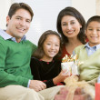 Family Sitting On Sofa Together,Holding A Christmas Gift — Stock Photo #4778314