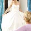 Bride trying on wedding dress with sales assistant — Stock Photo #4815590
