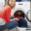 Woman Loading Clothes Into Washing Machine — Stock Photo #48298431
