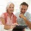 Middle Aged Couple Looking At Digital Tablet — Stock Photo #48299127