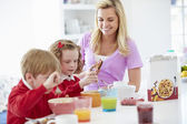 Mother And Children Having Breakfast — Stock Photo