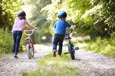 Two Children Pushing Bikes — Stock Photo